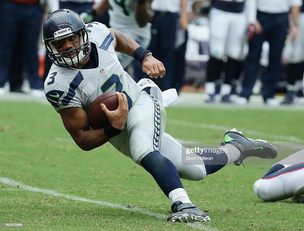 <a gi-track='captionPersonalityLinkClicked' href=/galleries/search?phrase=Russell+Wilson+-+American+Football+Quarterback&family=editorial&specificpeople=2292912 ng-click='$event.stopPropagation()'>Russell Wilson</a> #3 of the Seattle Seahawks fights for yards in the second half against the Houston Texans at Reliant Stadium on September 29, 2013 in Houston, Texas.