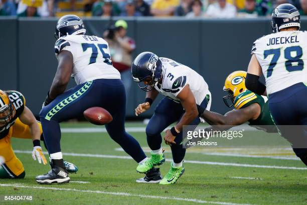 Russell Wilson of the Seattle Seahawks fumbles the football as he is hit by Mike Daniels of the Green Bay Packers during the third quarter at Lambeau...