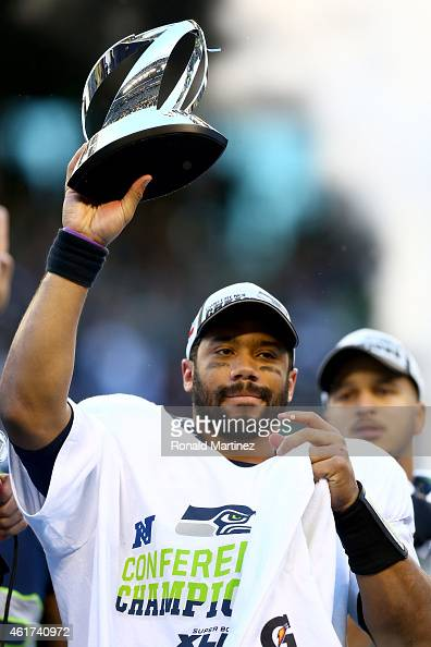 Russell Wilson of the Seattle Seahawks holds up the George S Halas trophy after the Seahawks defeated the Green Bay Packers in the 2015 NFC...
