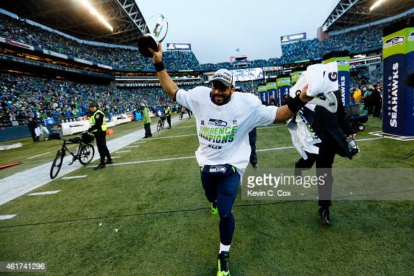 Russell Wilson of the Seattle Seahawks holds up the George S Halas trophy after the Seahawks 2822 overtime victory against the Green Bay Packers in...