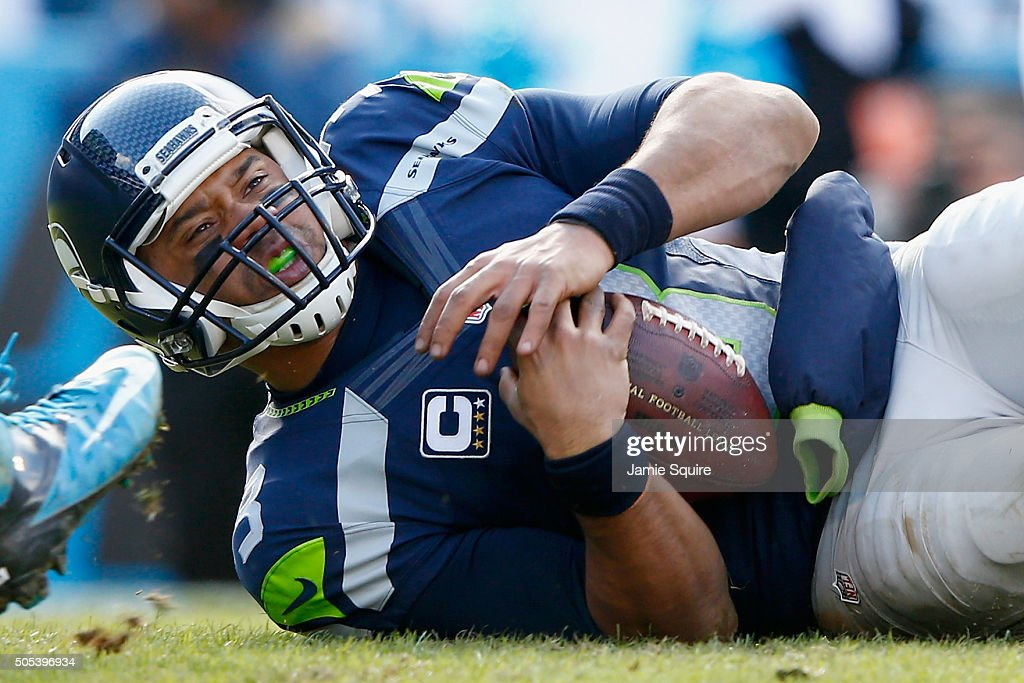 Russell Wilson of the Seattle Seahawks is knocked to the ground during the NFC Divisional Playoff Game against the Carolina Panthers at Bank of...