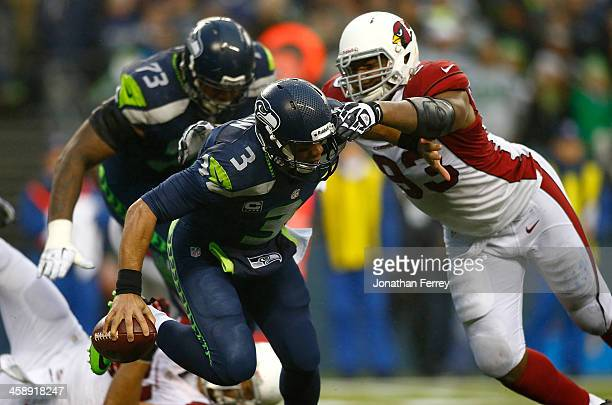Russell Wilson of the Seattle Seahawks is pressured by Calais Campbell of the Arizona Cardinals on December 22 2013 at CenturyLink Field in Seattle...