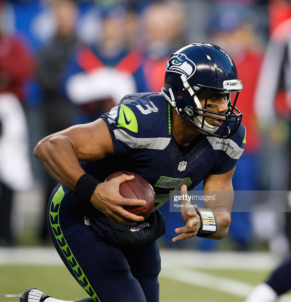 Russell Wilson #3 of the Seattle Seahawks is runs the ball against the St. Louis Rams in the first half at CenturyLink Field on December 30, 2012 in Seattle, Washington.
