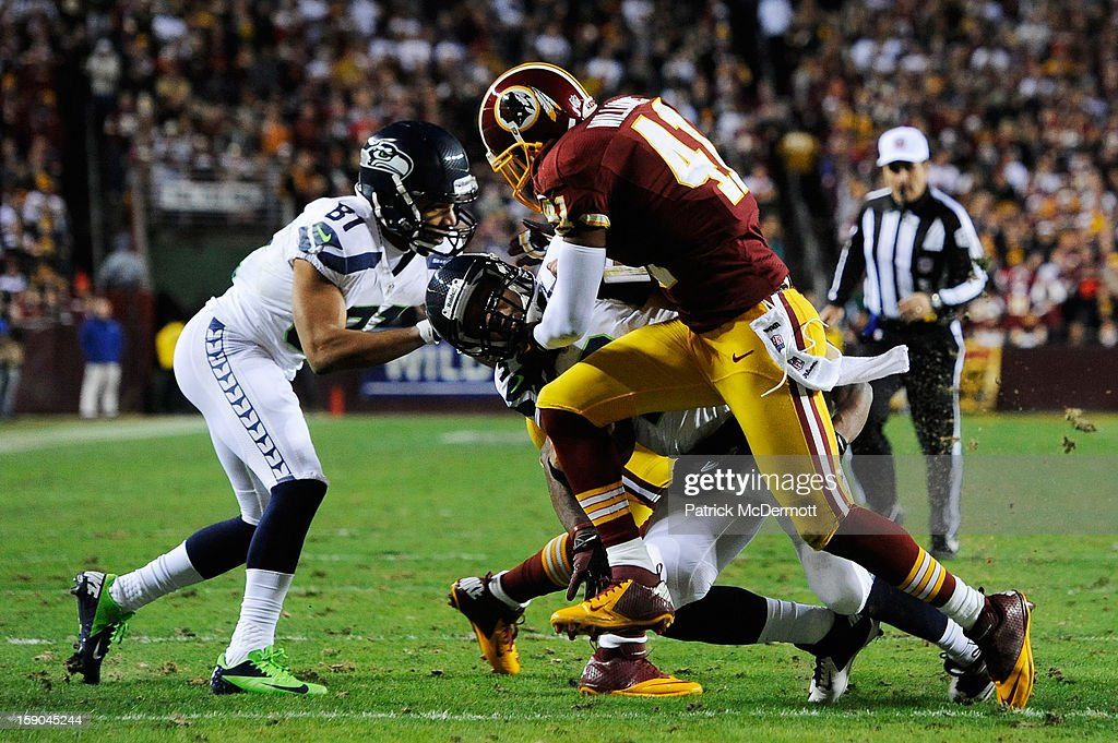 Russell Wilson #3 of the Seattle Seahawks is tackled by Madieu Williams #41 and DeAngelo Hall #23 of the Washington Redskins during the NFC Wild Card Playoff Game at FedExField on January 6, 2013 in Landover, Maryland.