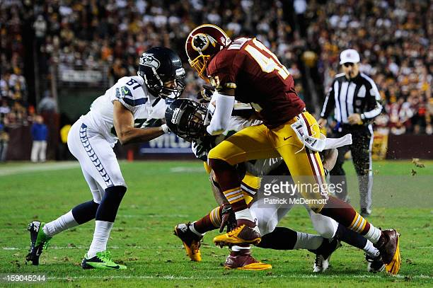Russell Wilson of the Seattle Seahawks is tackled by Madieu Williams and DeAngelo Hall of the Washington Redskins during the NFC Wild Card Playoff...