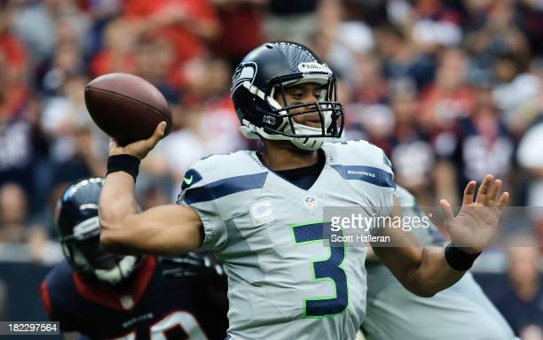Russell Wilson of the Seattle Seahawks looks to pass in the first half against the Houston Texans at Reliant Stadium on September 29 2013 in Houston...