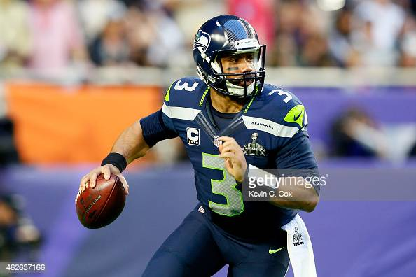 Russell Wilson of the Seattle Seahawks looks to pass in the first quarter against the New England Patriots during Super Bowl XLIX at University of...