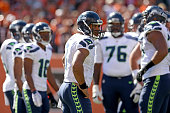 Russell Wilson of the Seattle Seahawks looks to the sideline for the play before relaying it to his teammates during the second quarter of the game...