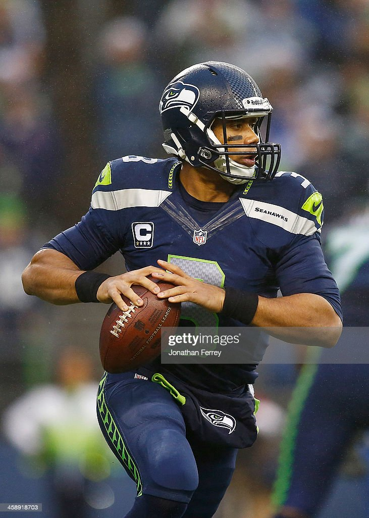 <a gi-track='captionPersonalityLinkClicked' href=/galleries/search?phrase=Russell+Wilson+-+American+Football+Quarterback&family=editorial&specificpeople=2292912 ng-click='$event.stopPropagation()'>Russell Wilson</a> #3 of the Seattle Seahawks looks to throw against the Arizona Cardinals on December 22, 2013 at CenturyLink Field in Seattle, Washington.
