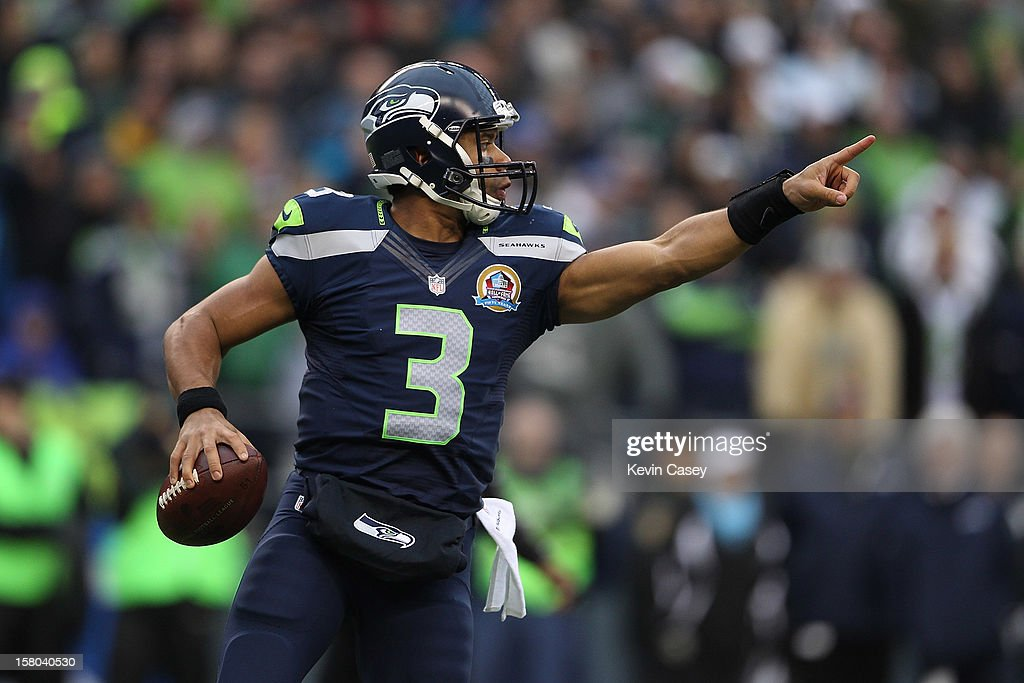 <a gi-track='captionPersonalityLinkClicked' href=/galleries/search?phrase=Russell+Wilson+-+Quarterback+de+futebol+americano&family=editorial&specificpeople=2292912 ng-click='$event.stopPropagation()'>Russell Wilson</a> #3 of the Seattle Seahawks points downfield against the Arizona Cardinals in the first quarter at CenturyLink Field on December 9, 2012 in Seattle, Washington.