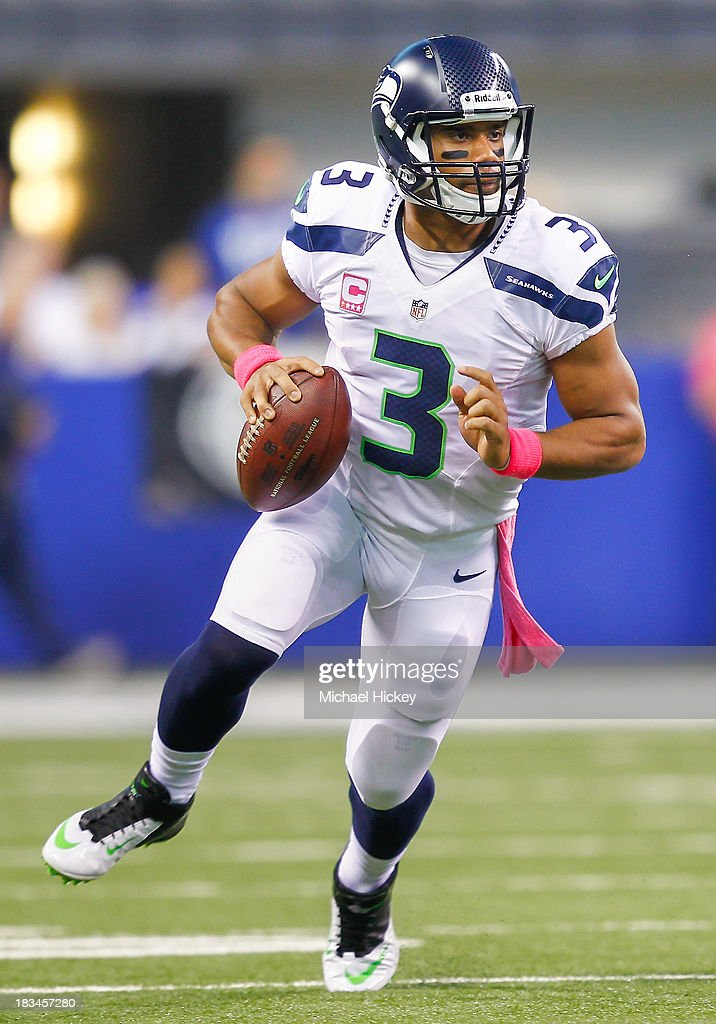 <a gi-track='captionPersonalityLinkClicked' href=/galleries/search?phrase=Russell+Wilson+-+American+Football+Quarterback&family=editorial&specificpeople=2292912 ng-click='$event.stopPropagation()'>Russell Wilson</a> #3 of the Seattle Seahawks rolls out of the pocket against the Indianapolis Colts at Lucas Oil Stadium on October 6, 2013 in Indianapolis, Indiana. Indianapolis defeated Seattle 34-28.