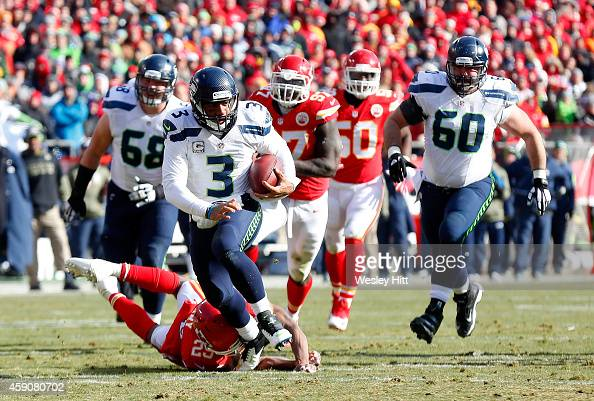 Russell Wilson of the Seattle Seahawks runs the ball past Eric Berry of the Kansas City Chiefs during the game at Arrowhead Stadium on November 16...