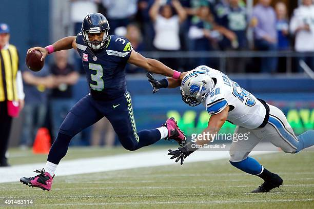 Russell Wilson of the Seattle Seahawks runs with the ball as Travis Lewis of the Detroit Lions defends during the game at CenturyLink Field on...