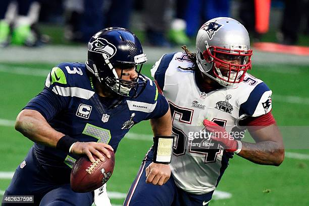 Russell Wilson of the Seattle Seahawks scrambles with the ball against Dont'a Hightower of the New England Patriots in the first quarter during Super...
