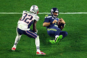 Russell Wilson of the Seattle Seahawks slides after a run against Devin McCourty of the New England Patriots in the third quarter during Super Bowl...
