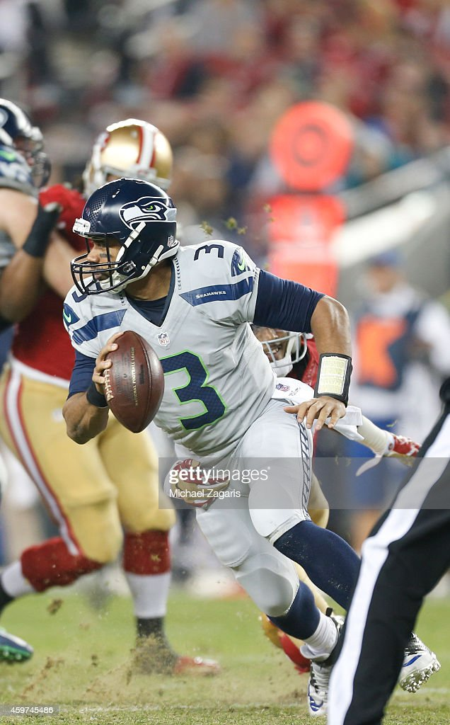 <a gi-track='captionPersonalityLinkClicked' href=/galleries/search?phrase=Russell+Wilson+-+American+Football+Quarterback&family=editorial&specificpeople=2292912 ng-click='$event.stopPropagation()'>Russell Wilson</a> #3 of the Seattle Seahawks spins away from <a gi-track='captionPersonalityLinkClicked' href=/galleries/search?phrase=Dontae+Johnson&family=editorial&specificpeople=7199526 ng-click='$event.stopPropagation()'>Dontae Johnson</a> #36 of the San Francisco 49ers during the game at Levi Stadium on November 27, 2014 in Santa Clara, California. The Seahawks defeated the 49ers 19-3.