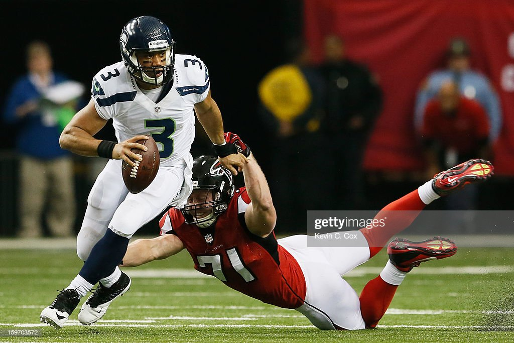 Russell Wilson #3 of the Seattle Seahawks tries to avoid the tackle of Kroy Biermann #71 of the Atlanta Falcons during the NFC Divisional Playoff Game at Georgia Dome on January 13, 2013 in Atlanta, Georgia.