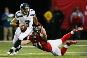 Russell Wilson of the Seattle Seahawks tries to avoid the tackle of Kroy Biermann of the Atlanta Falcons during the NFC Divisional Playoff Game at...