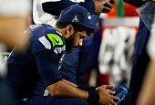 Russell Wilson of the Seattle Seahawks waits on the sidelines in the fourth quarter against the New England Patriots during Super Bowl XLIX at...