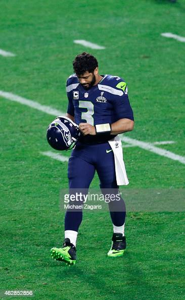 Russell Wilson of the Seattle Seahawks walks off the field after throwing an interception that cost the Seahawks the game during the game against the...