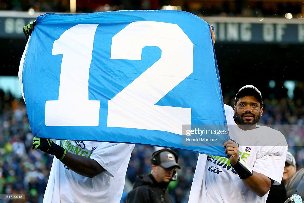 Russell Wilson #3 of the Seattle Seahawks waves the 12th Man flag after the Seahawks defeated the Green Bay Packers in the 2015 NFC Championship game at CenturyLink Field on January 18, 2015 in Seattle, Washington.