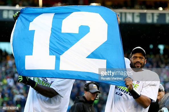 Russell Wilson of the Seattle Seahawks waves the 12th Man flag after the Seahawks defeated the Green Bay Packers in the 2015 NFC Championship game at...