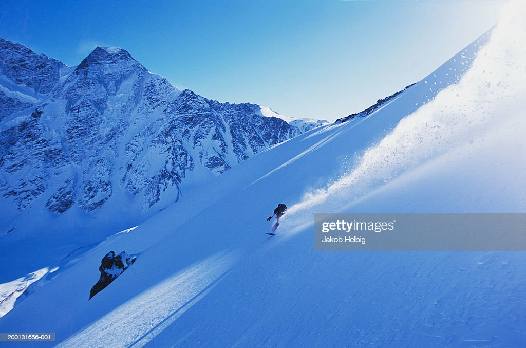 Russia, Caucasus Mountains, male snowboarder descending Mount Cheget : Stock Photo