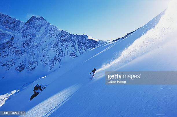 Russia, Caucasus Mountains, male snowboarder descending Mount Cheget