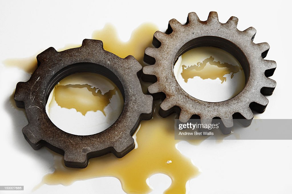 USA & Russia formed in oil between 2 gear cogs : Stock Photo