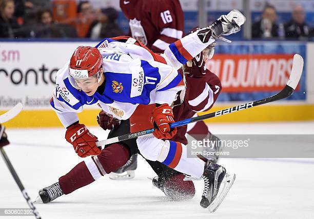 Russia forward German Rubtsov is upended by Latvia defenceman Maksims Ponomarenko in the second period during the World Junior Hockey Championships...