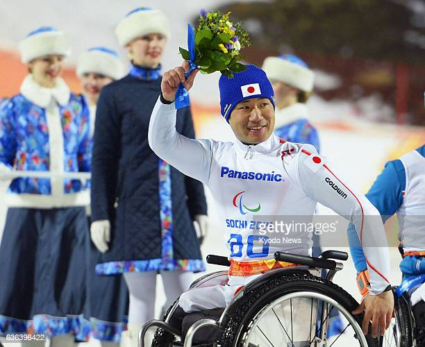 SOCHI Russia Gold medalist Takeshi Suzuki of Japan waves to supporters during a flower ceremony for the alpine skiing men's sitting slalom event at...