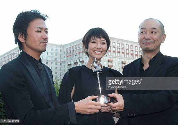 MOSCOW Russia Japan actor Shima Onishi actress Yoko Maki and movie director Tatsushi Omori hold a trophy in Moscow on June 29 after 'The Ravine of...
