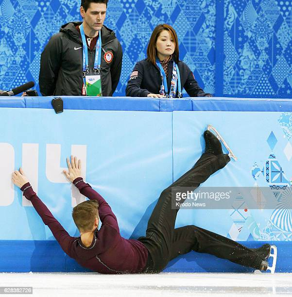 SOCHI Russia Jeremy Abbott of the United States takes a tumble during his performance in the men's figure skating short program as his coach Yuka...