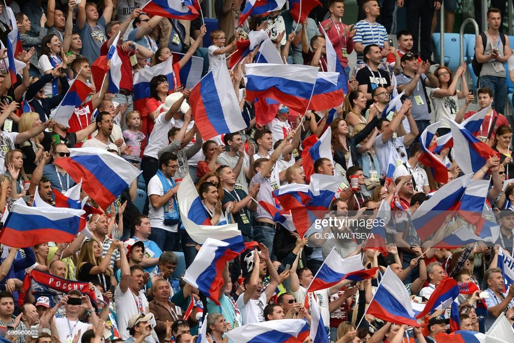 TOPSHOT - Russia supporters cheer during the 2017 Confederations Cup group A football match between Russia and New Zealand at the Krestovsky Stadium in Saint-Petersburg on June 17, 2017. / AFP PHOTO / Olga MALTSEVA