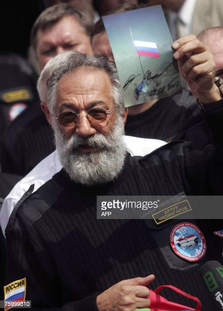 Russian adventurer and Duma deputy Artur Chilingarov holds up a photo of the flag he planted in the North Pole upon his arrival in Moscow 07 August...