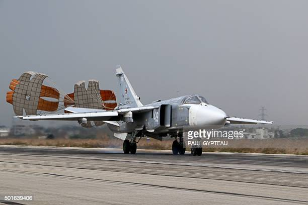 A Russian Sukhoi Su24 bomber lands at the Russian Hmeimim military base in Latakia province in the northwest of Syria on December 16 2015 Russia...