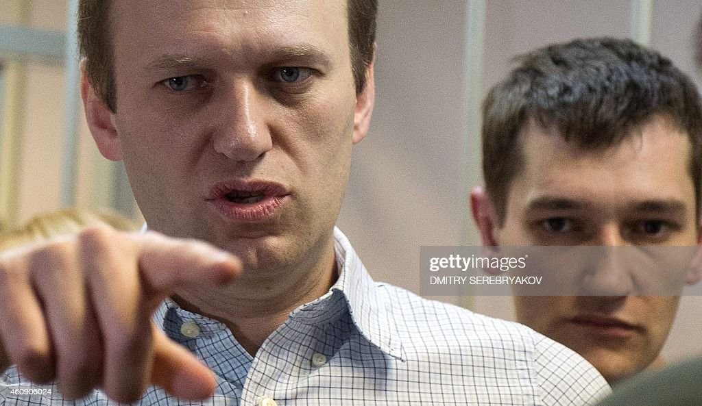 Russian anti-Kremlin opposition leader <a gi-track='captionPersonalityLinkClicked' href=/galleries/search?phrase=Alexei+Navalny&family=editorial&specificpeople=6849046 ng-click='$event.stopPropagation()'>Alexei Navalny</a> (L) gestures next to his brother and co-defendant Oleg as they attend the verdict announcement of their fraud trial at a court in Moscow on December 30, 2014. Russia's top opposition leader <a gi-track='captionPersonalityLinkClicked' href=/galleries/search?phrase=Alexei+Navalny&family=editorial&specificpeople=6849046 ng-click='$event.stopPropagation()'>Alexei Navalny</a> on December 30 called for mass protests to 'destroy' President Vladimir Putin's regime after a court handed him a suspended sentence but jailed his brother in a controversial fraud case. In a lightning hearing that was abruptly brought forward by two weeks, a judge found both Navalny and his brother Oleg guilty of embezzlement and sentenced the siblings to three and a half years in what is widely seen as a politically motivated case. AFP PHOTO / DMITRY SEREBRYAKOV