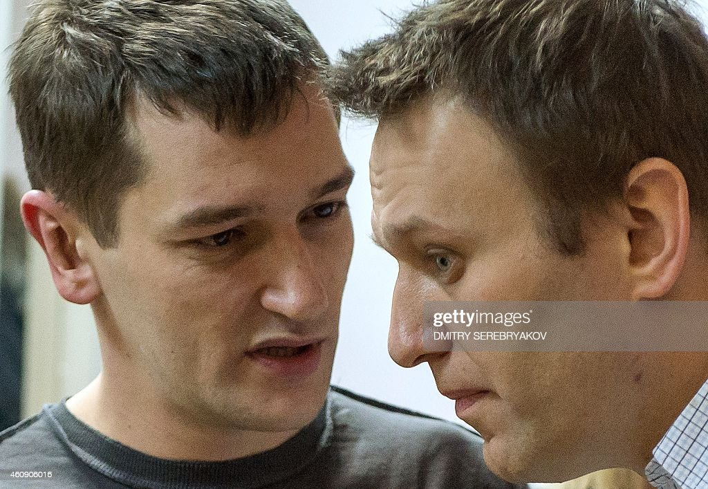 Russian anti-Kremlin opposition leader Alexei Navalny (R) listens to his brother and co-defendant Oleg as they attend the verdict announcement of their fraud trial at a court in Moscow on December 30, 2014. Russia's top opposition leader Alexei Navalny on December 30 called for mass protests to 'destroy' President Vladimir Putin's regime after a court handed him a suspended sentence but jailed his brother in a controversial fraud case. In a lightning hearing that was abruptly brought forward by two weeks, a judge found both Navalny and his brother Oleg guilty of embezzlement and sentenced the siblings to three and a half years in what is widely seen as a politically motivated case. AFP PHOTO / DMITRY SEREBRYAKOV
