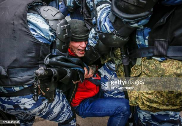 TOPSHOT Russian antiriot policemen detain a demonstrator taking part in a nationalist march during the National Unity Day in Moscow on November 04...