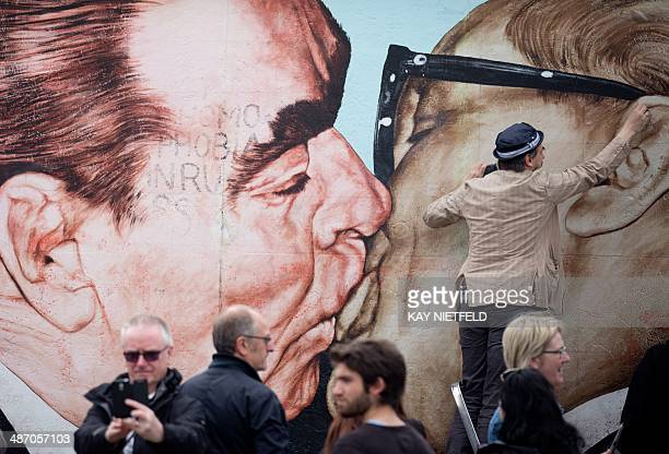 Russian artist Dmitri Vrubel cleans his painting 'My God help me to survive this deadly love' at the East side gallery from tags and scribblings in...