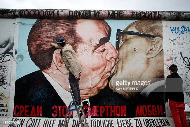 Russian artist Dmitri Vrubel cleans with his son his painting 'My God help me to survive this deadly love' at the East side gallery from tags and...