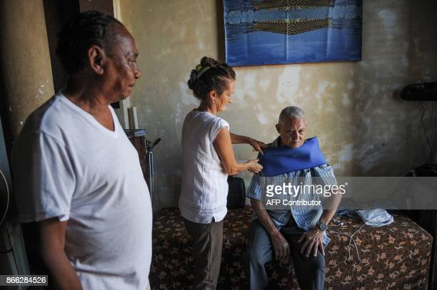 Russian astronomer Svelana Oparina and her Cuban husband bioenergetic doctor Eugenio Reyes treat a patient at their house in Havana on October 16...