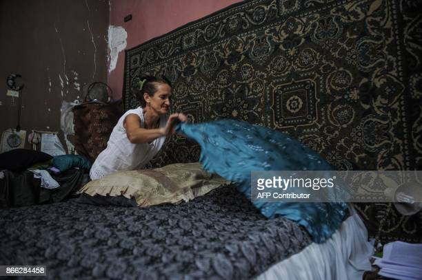 Russian astronomer Svelana Oparina married to a Cuban bioenergetic doctor makes her bed at their house in Havana on October 16 2017 With three...