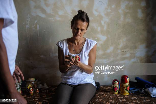 Russian astronomer Svelana Oparina married to a Cuban bioenergetic doctor handles Russian Matryoshka dolls at her house in Havana on October 16 2017...