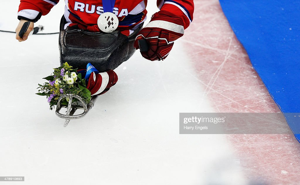 A Russian athlete with a silver medal leaves the rink after losing the Ice Sledge Hockey Gold Medal match between Russia and USA at the Shayba Arena during day eight of the 2014 Paralympic Winter Games on March 15, 2014 in Sochi, Russia.