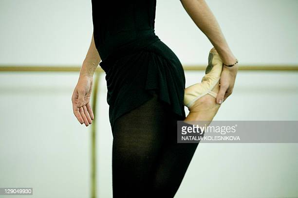 A Russian ballerina stretches during a rehearsal at the Bolshoi Theatre in Moscow on October 12 2011 After years of closure for renovation the main...