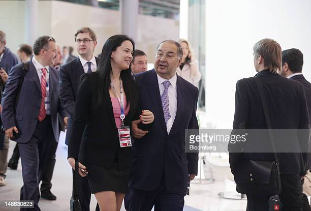 Russian billionaire Alisher Usmanov center arrives in an exhibition hall on day one of the Saint Petersburg International Economic Forum 2012 in...