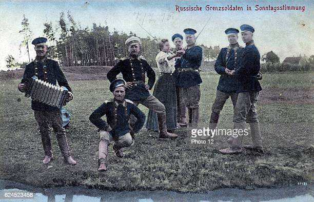 1900 Russian border guards and one woman in dance poses with one border guard playing accordion