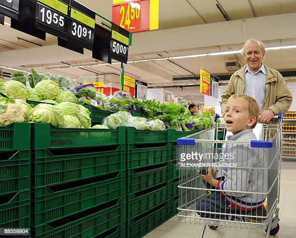 A Russian boy rides in a shopping cart at the newlyopened Carrefour hypermarket in Moscow on June 18 2009 French giant Carrefour has opened its first...