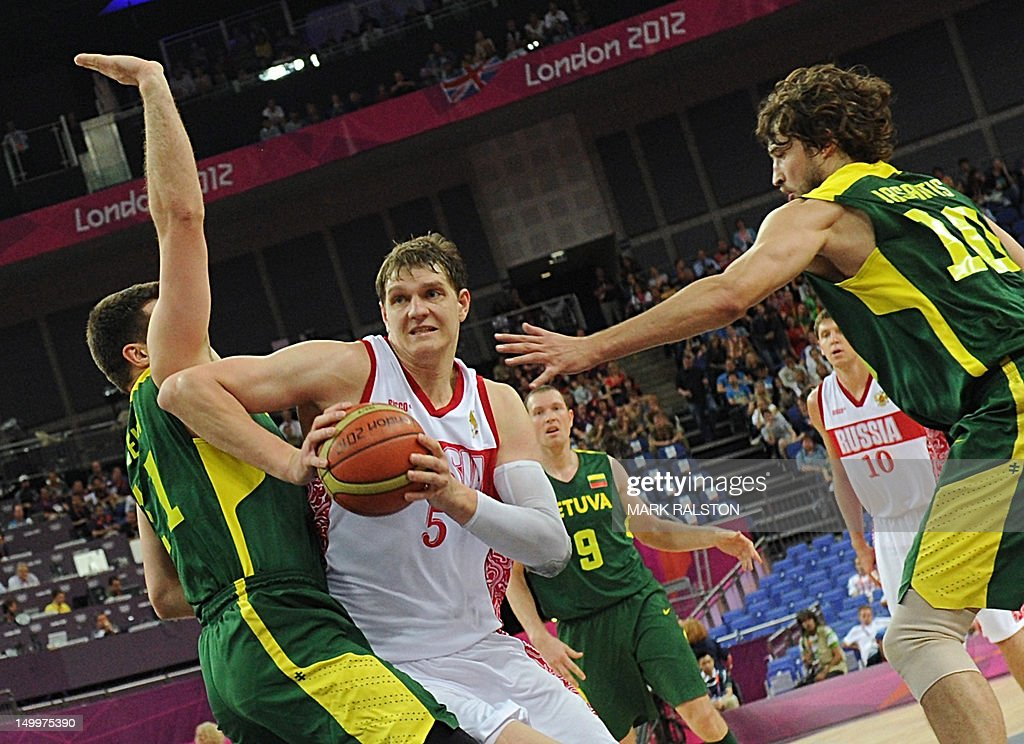Russian centre Timofey Mozgov (C) is challenged by Lithuanian forward Linas Kleiza (L) and Lithuanian forward Simas Jasaitis (R) during their London 2012 Olympic Games men's quarterfinal basketball match in London on August 8, 2012.
